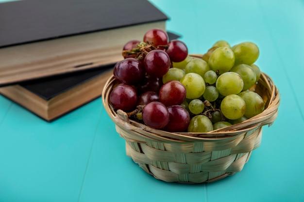 青い背景の閉じた本とバスケットのブドウの側面図 無料写真