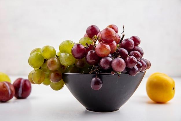 白い背景のプルオットとネクタコットとボウルのブドウの側面図 無料写真
