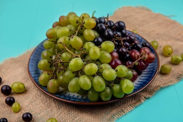 青い背景の荒布にブドウの果実とプレートのブドウの側面図 無料写真