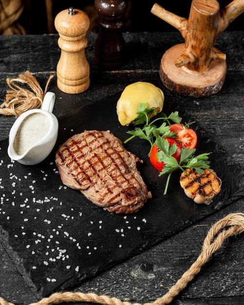 Вид сбоку на гриле стейк из говядины с овощами петрушкой и соусом на черной доске Бесплатные Фотографии