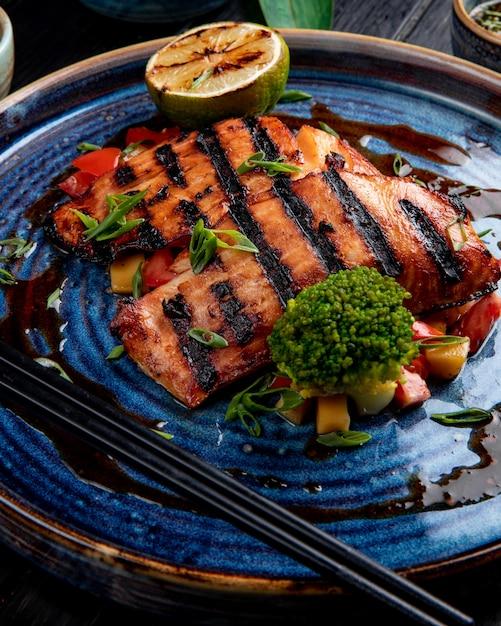 木製のテーブルの皿の上の野菜レモンと醤油焼きサーモンの側面図 無料写真