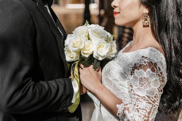 신랑과 신부 꽃의 꽃다발을 들고의 측면보기 무료 사진