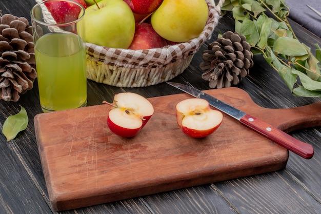Вид сбоку наполовину разрезанного яблока и ножа на разделочной доске с яблочным соком и корзиной яблочного шишка Бесплатные Фотографии