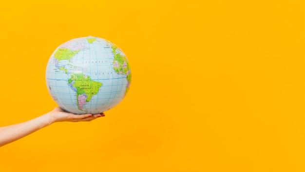 Вид сбоку руки, держащей земной шар с копией пространства Бесплатные Фотографии
