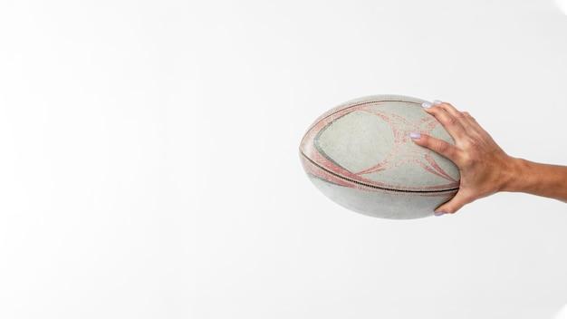 Вид сбоку руки, держащей мяч для регби с копией пространства Бесплатные Фотографии