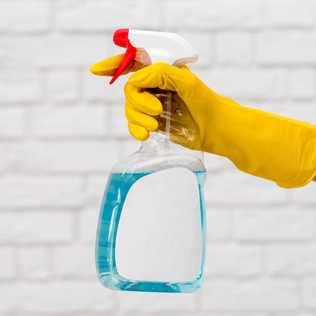Вид сбоку руки с перчаткой, холдинг моющего раствора Бесплатные Фотографии