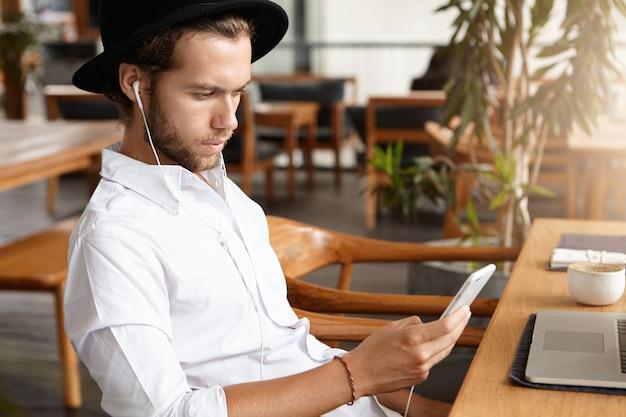 Взгляд со стороны красивого бородатого человека в черной шляпе и белых наушниках звоня видео- к его партнеру используя мобильный телефон. кавказский студент слушает музыку, ждет своего друга в кафе Бесплатные Фотографии