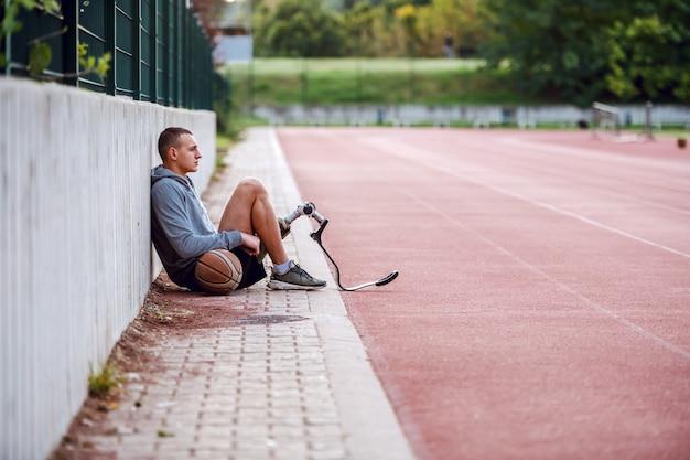 スポーツウェアとバスケットボールボールの競馬場に座っている義足でハンサムなフィット深刻なスポーツ障害者の側面図です。 Premium写真
