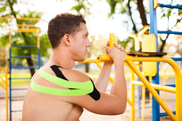 스포츠 그라운드에서 포즈 어깨에 검은 색과 녹색 탄성 테이프와 잘 생긴 젊은 백인 전문 보디의 측면보기 프리미엄 사진