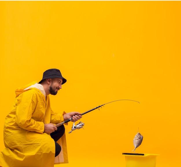 キャッチで釣り竿を保持している幸せな漁師の側面図 無料写真