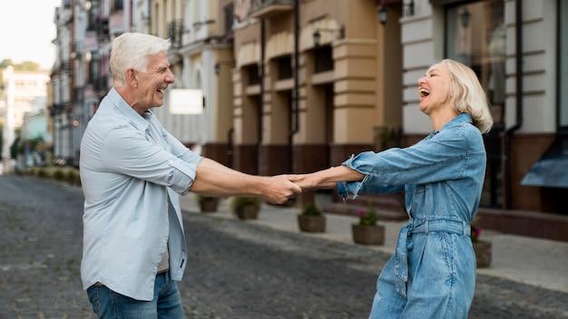 Вид сбоку счастливой старшей пары, проводящей время в городе Бесплатные Фотографии