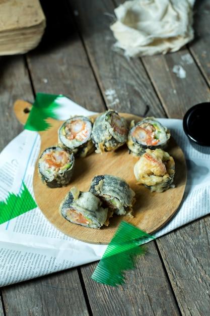 日本の伝統的な料理の天ぷら寿司マキの側面図を木の板に生姜と醤油を添えて 無料写真