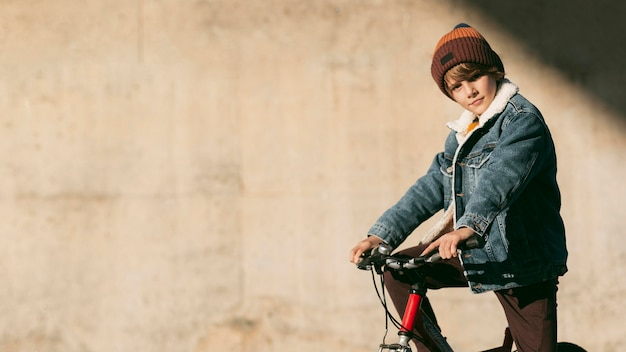 コピースペースと屋外の自転車に乗っている子供の側面図 無料写真