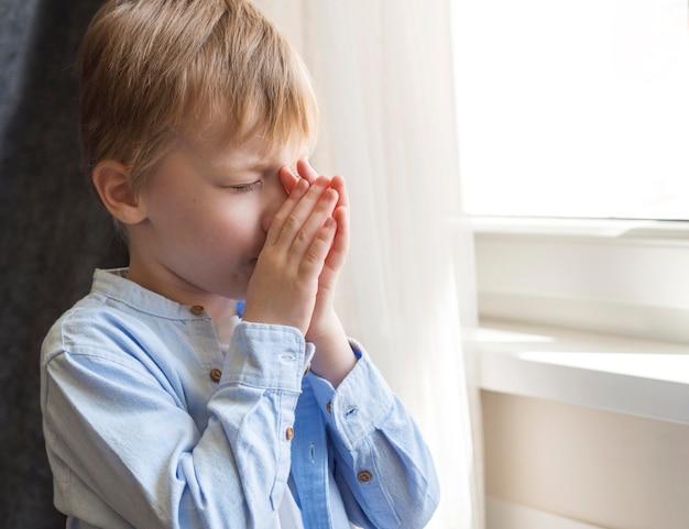 祈る少年の側面図 無料写真