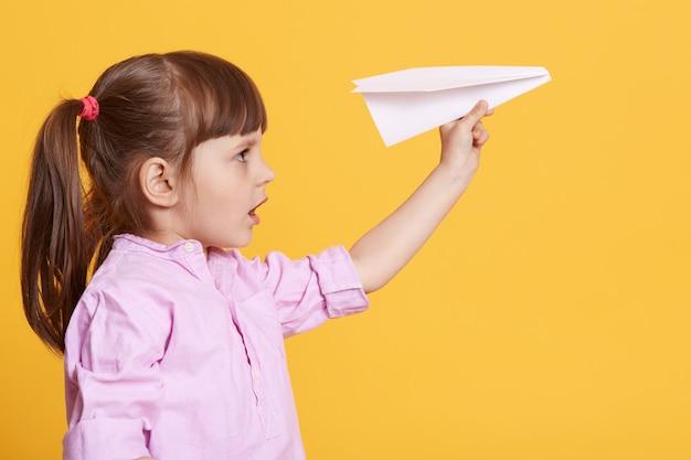 손에 흰 종이 비행기와 함께 포즈를 취하는 작은 귀여운 여자 아이의 모습 프리미엄 사진