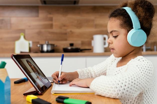 タブレットでオンライン学校中の少女の側面図 無料写真
