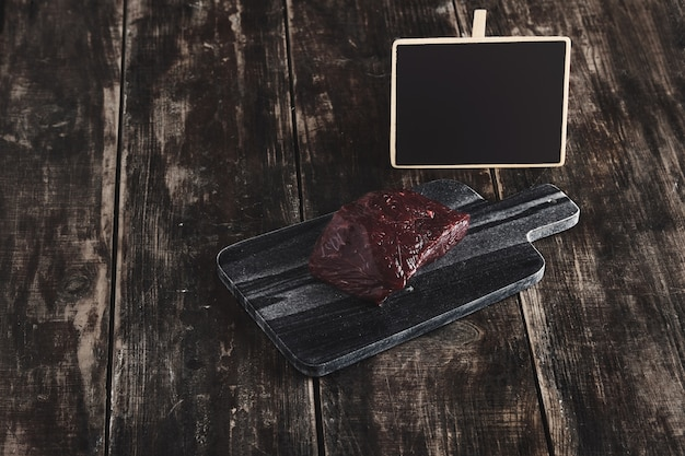 黒い大理石の石のカッティングデスクと熟成したヴィンテージの木製テーブルとチョークボードの値札の上の鯨肉ステーキの豪華な生の部分の側面図 無料写真