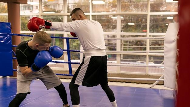 トレーナーと練習している男性ボクサーの側面図 Premium写真