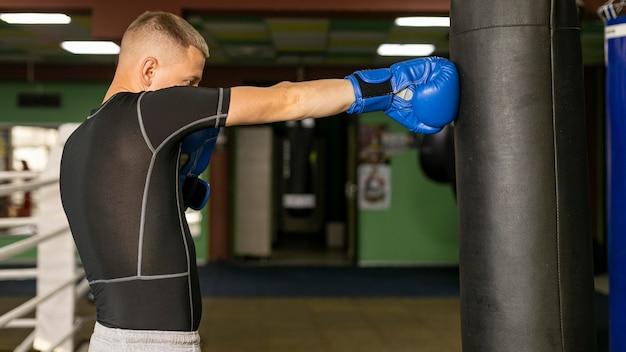 手袋のトレーニングと男性ボクサーの側面図 無料写真