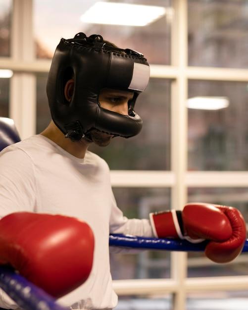リングにヘルメットを持つ男性ボクサーの側面図 無料写真