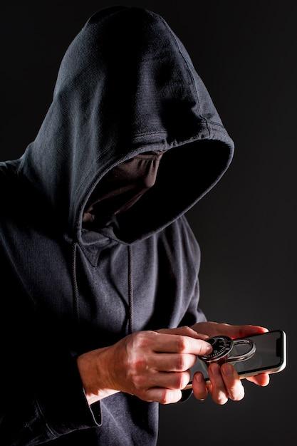 Вид сбоку мужской хакер, держа смартфон и замок Бесплатные Фотографии