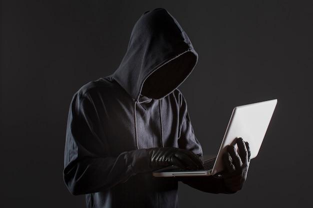 Вид сбоку мужской хакер с перчатками и ноутбук Бесплатные Фотографии