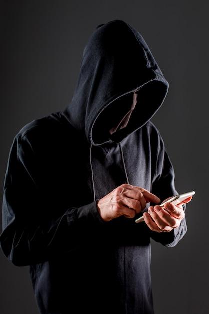 Вид сбоку мужской хакер с смартфона Бесплатные Фотографии