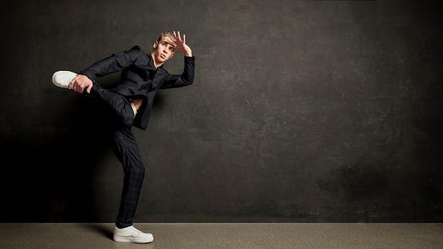 Вид сбоку мужской исполнитель в костюме позирует с копией пространства Бесплатные Фотографии