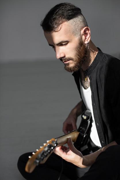 Вид сбоку мужчины-исполнителя, играющего на электрогитаре Бесплатные Фотографии