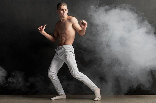 Вид сбоку мужской исполнитель позирует в джинсах с дымом и копией пространства Бесплатные Фотографии