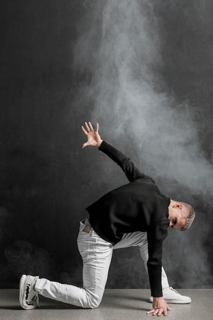 Вид сбоку мужской исполнитель позирует в джинсах с дымом Premium Фотографии