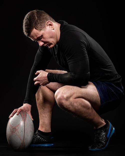 Вид сбоку игрока в регби, держащего мяч одной рукой Бесплатные Фотографии