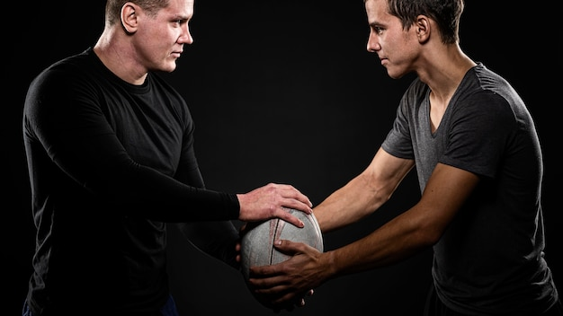 Вид сбоку игроков мужского пола в регби, держащих мяч Бесплатные Фотографии