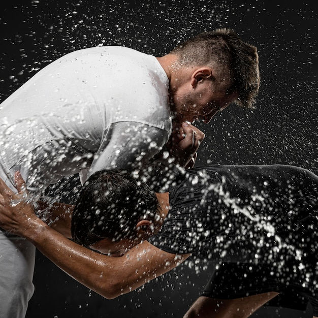 Вид сбоку игроков мужского пола в регби с мячом и брызгами воды Бесплатные Фотографии