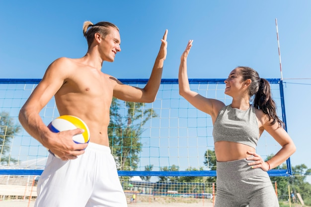 バレーボールをプレイしながらお互いにハイタッチする男女の側面図 無料写真