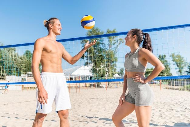 Вид сбоку мужчины и женщины на пляже, играя в волейбол Бесплатные Фотографии