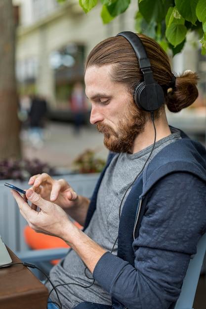 Вид сбоку человека на городской террасе с смартфоном и наушниками Бесплатные Фотографии