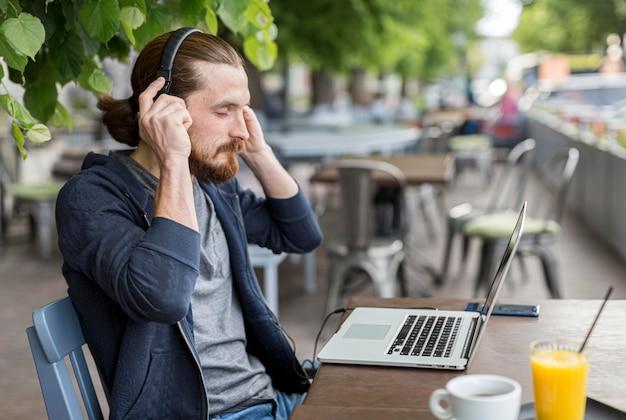 Вид сбоку человека на террасе с наушниками и ноутбуком Бесплатные Фотографии