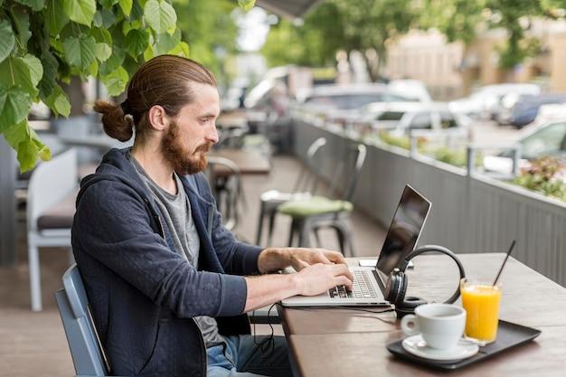 Вид сбоку человека на террасе работает на ноутбуке Бесплатные Фотографии