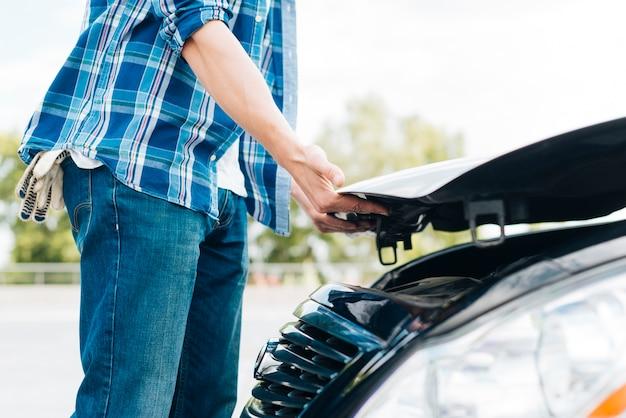 車のボンネットを閉じる男の側面図 無料写真