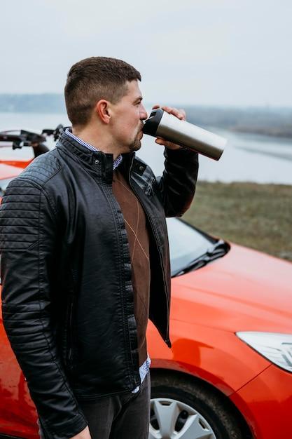 Вид сбоку человека, пьющего рядом с машиной Бесплатные Фотографии