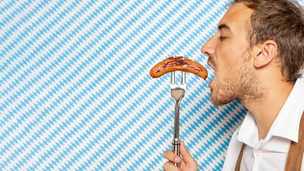 ドイツのソーセージを食べている男の側面図 無料写真