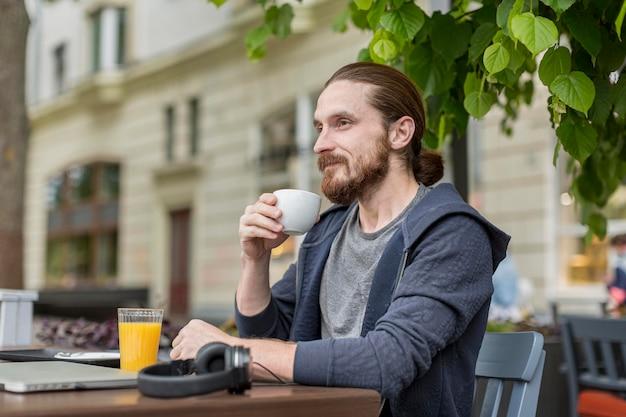 Боковой вид человека, наслаждаясь кофе на городской террасе Бесплатные Фотографии