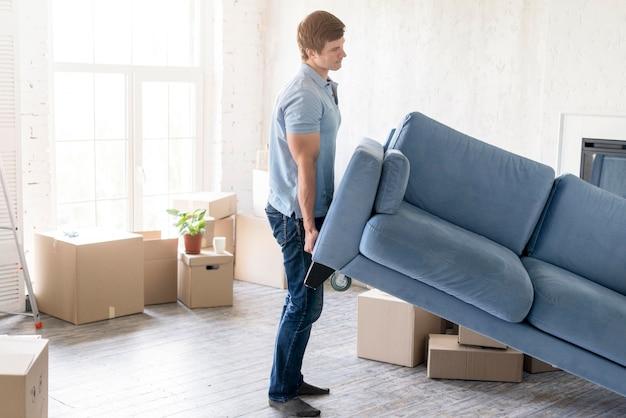 Вид сбоку на человека, занимающегося диваном во время подготовки к выезду Бесплатные Фотографии
