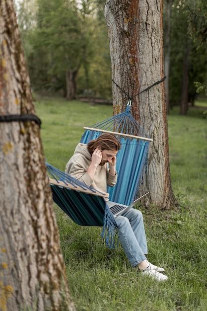 自然の中でハンモックで男の側面図 無料写真
