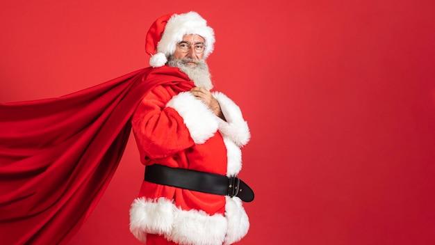 コピースペースとギフトバッグを保持しているサンタ衣装の男の側面図 Premium写真