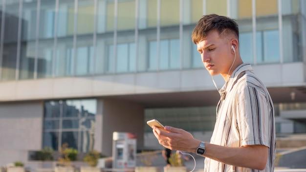 Вид сбоку на человека в городе, слушающего музыку в наушниках Бесплатные Фотографии