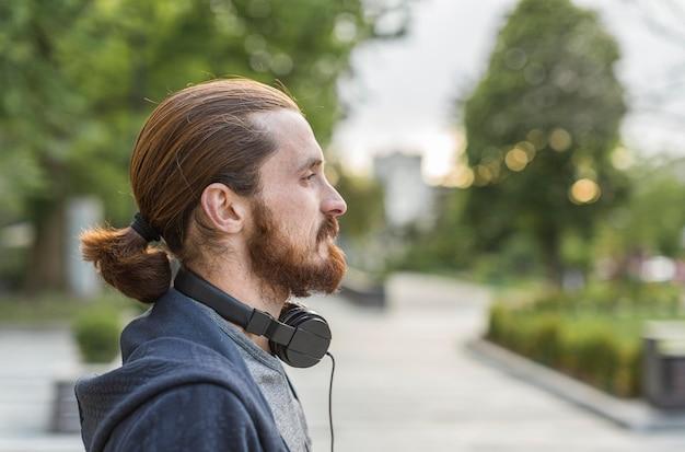 Боковой вид человека в городе с наушниками Бесплатные Фотографии