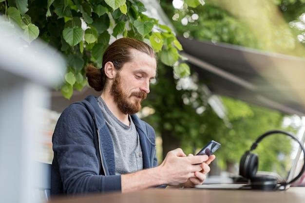 Вид сбоку человека в городе с смартфон и наушники Бесплатные Фотографии