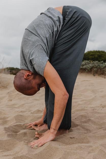 Вид сбоку человека в позе йоги на открытом воздухе Бесплатные Фотографии